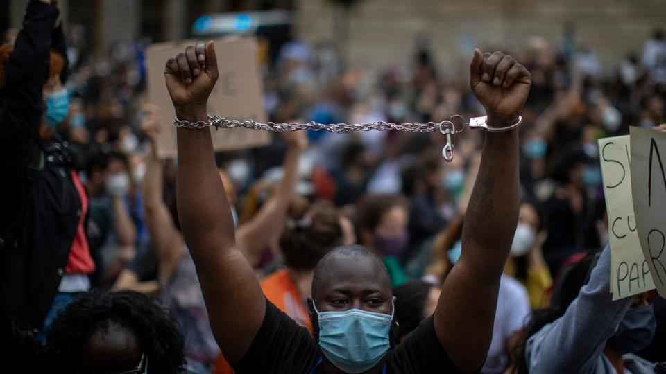 İnsanlar, Minneapolis polisi tarafından sınırlandırıldıktan sonra ölen siyah bir adam olan George Floyd'un ölümü üzerine bir gösteri sırasında İspanya'nın Barselona kentinde toplanıyor. 7 Haziran 2020.