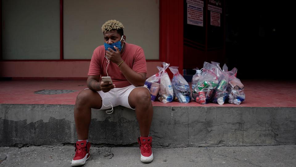 30 yaşındaki şarkıcı Hector Leon, 25 Mayıs 2020, Küba'nın merkezinde, koronavirüs hastalığı (Covid-19) salgınının yayılmasıyla ilgili endişeleri üzerine çevrimiçi satın aldığı ürünleri aldıktan sonra akıllı telefonundan İnternet üzerinden konuşuyor.