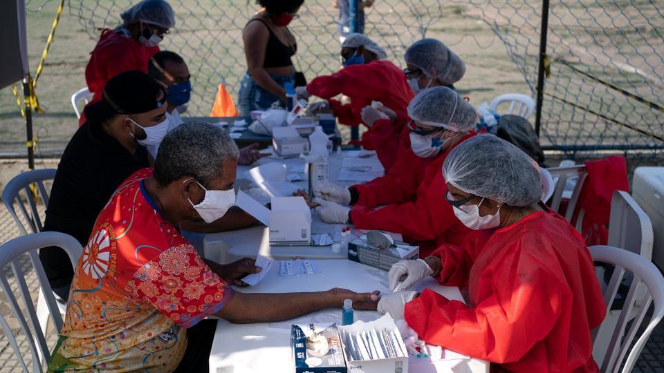 Bir sağlık çalışanı, 8 Haziran 2020 Pazartesi, Brezilya, Duque de Caxias'taki bir plazadaki yeni koronavirüs pandemisinin ortasında Covid-19'u test etmek için bir insandan kan örneği alıyor.