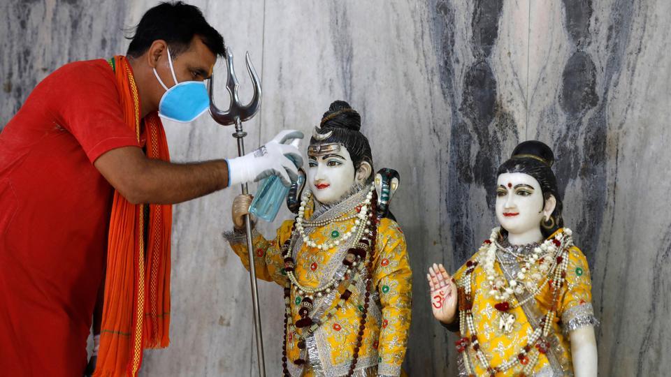 Hintli bir rahip Lord Shiva ve Tanrıça Parvati'nin idolünü 8 Haziran 2020 Pazartesi, Prayagraj, Hindistan'daki bir tapınakta temizler.