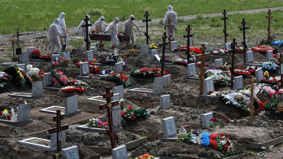 Kişisel koruyucu ekipman (KKE) giyen mezar kazıcılar muhtemelen 10 Haziran 2020, Saint Petersburg eteklerinde bir mezarlığın özel amaçlı bölümünde koronavirüs hastalığından (Covid-19) ölen bir kişinin tabutunu taşırlar.