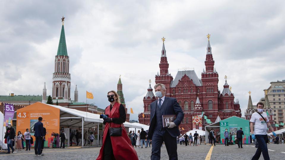 Koronavirüse karşı korunmak için yüz maskeleri takan insanlar, 6 Haziran 2020 Cumartesi günü Moskova, Rusya'da arka planda bir Tarihi müzesi ile Kızıl Meydan'da kurulmuş bir açık kitap pazarına girerler.