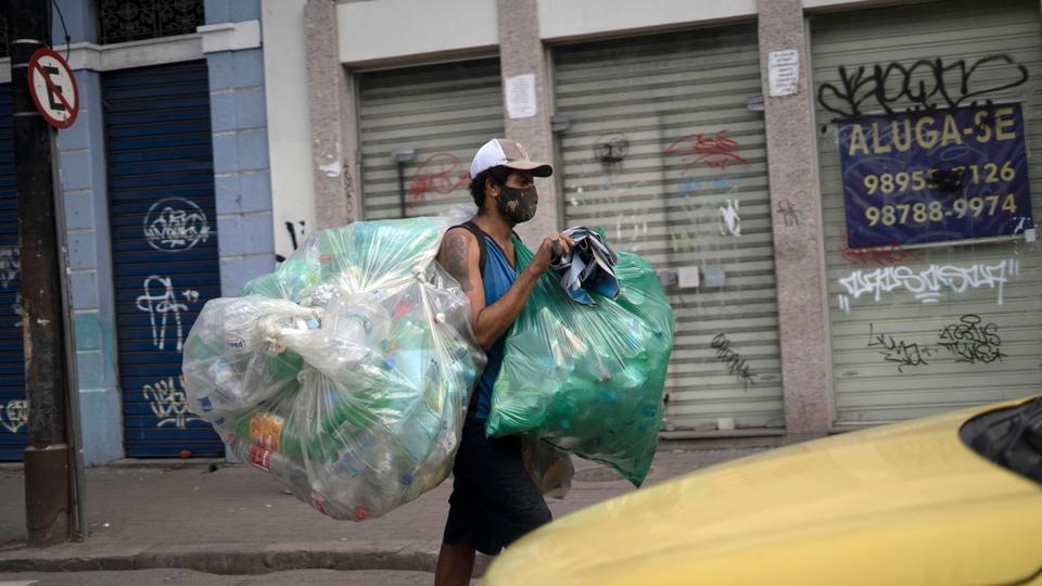 Bir geri dönüşümcü 17 Haziran 2020'de Rio de Janeiro, Brezilya'daki Covid-19 salgınıyla ilgili bir yüz maskesi takıyor.