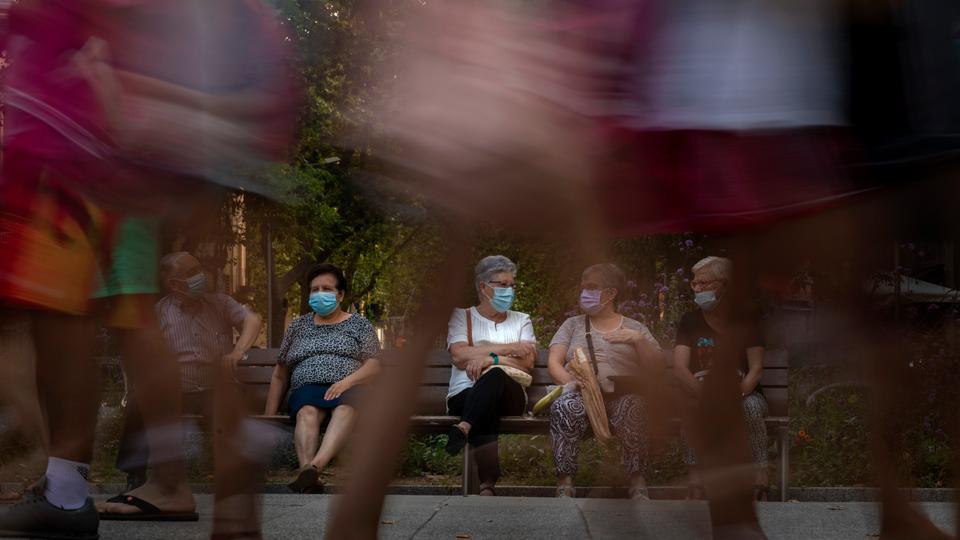 Yayalar, 21 Haziran 2020'de İspanya'nın Barselona kentinde bir bankta oturup geçmişte yürüyorlar