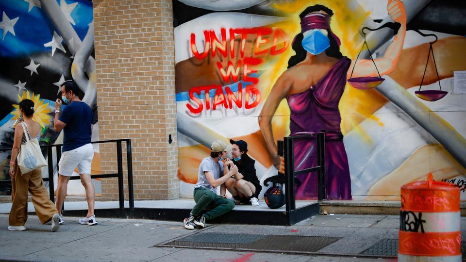 Yayalar, 22 Haziran 2020'de New York'un SoHo semtinde, işletmelerin mağaza önlerini kaplayan tahtalara boyanmış sokak sanatının yanında oturuyorlar.