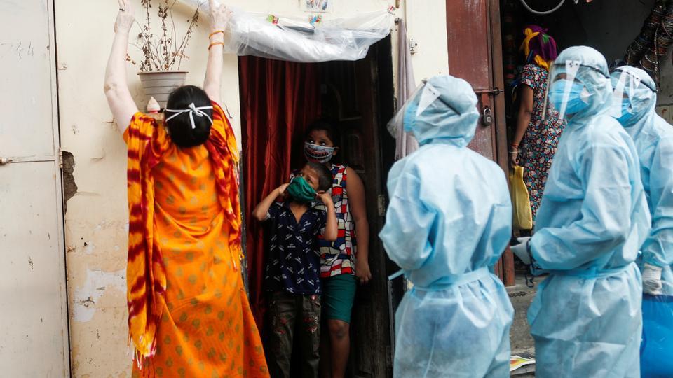 Kişisel koruyucu ekipman (PPE) giyen sağlık çalışanları, Mumbai, Hindistan'daki koronavirüs hastalığı (Covid-19) için bir kontrol kampı sırasında sakinlerin sıcaklığını kontrol edebilmeleri için bir kadın evin girişinde koruyucu bir tabaka oluşturur. , 2020.