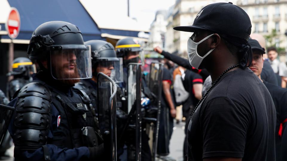 Bir gösterici, 20 Haziran 2020'de Paris, Fransa'da polis vahşeti, ırksal eşitsizliğe karşı bir protesto sırasında Fransız CRS çevik kuvvet polisi ile karşı karşıya.