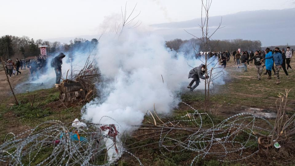 A migrant throws back a tear gas canister as they clash with Greek riot police on the Turkish-Greek border near Turkey's Pazarkule border crossing with Greece's Kastanies, in Edirne, Turkey, March 7, 2020.