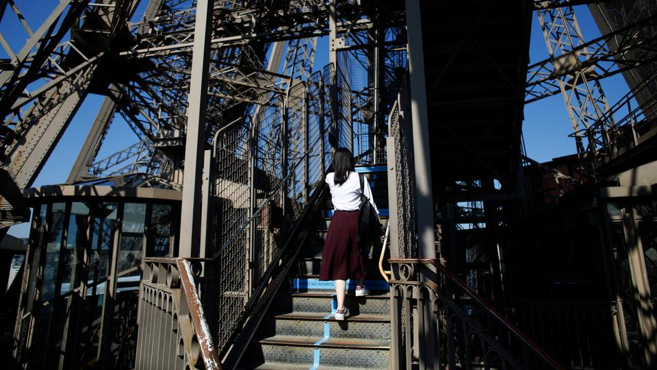 Bir ziyaretçi 25 Haziran 2020 Perşembe günü Paris'te Eyfel Kulesi'nin merdivenlerine tırmanıyor.