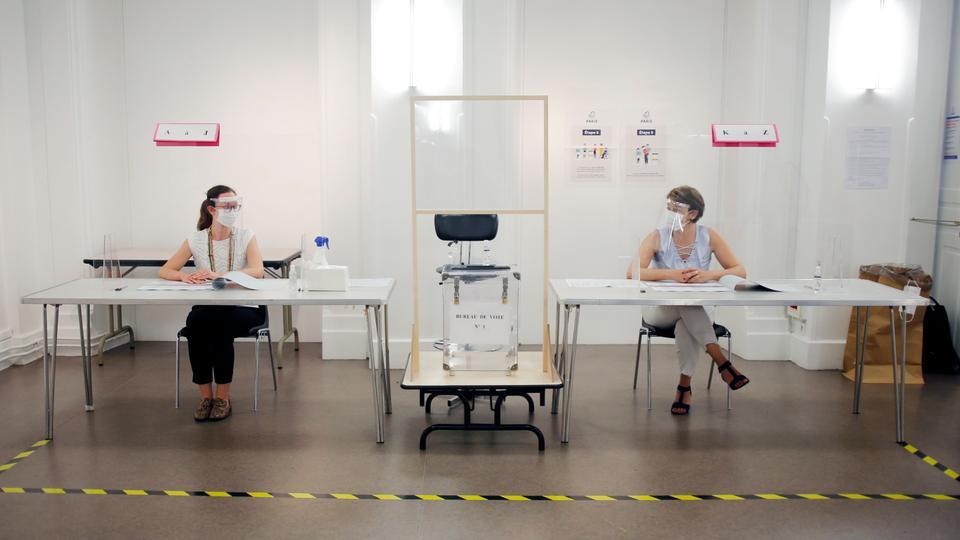 Koronavirüse karşı korunmak için yüz maskesi ve vizör takan insanlar, 26 Haziran 2020'de Paris, Fransa'da 28 Haziran Pazar günü yapılması planlanan yerel seçimler için yapılacak bir prova sırasında cam bir kalkanın arkasında oturuyorlar.
