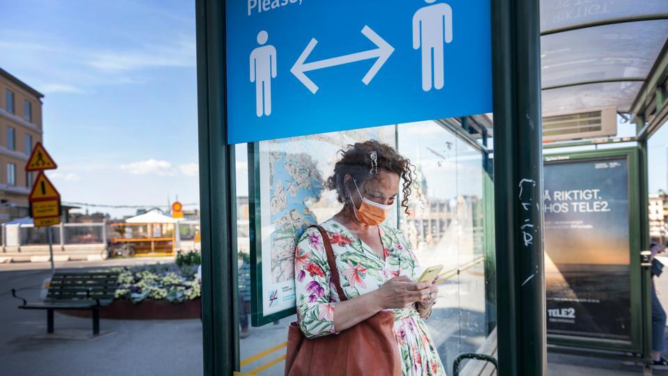 26 Haziran 2020 Stockholm, İsveç'teki Covid-19 nedeniyle sosyal mesafeyi korumaya çalışan bir bilgi işaretinin yanında bir otobüs durağında yüz maskesi giyen bir kadın görülür.