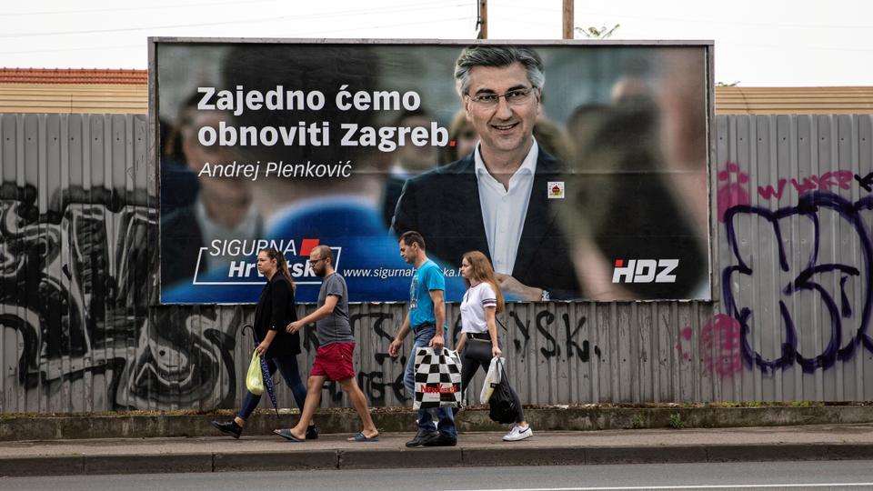 İnsanlar Hırvatistan Başbakanı ve merkez sağ Hırvat Demokrat Birliği (HDZ) Andrej Plenkoviç'in kampanyasını ilan eden bir pankartın önünden geçerek 3 Temmuz 2020'de Zagrzeb'deki parlamento seçimleri öncesinde.