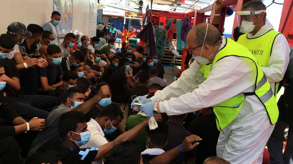 Bir İtalyan sağlık çalışanı, 5 Temmuz 2020'de Akdeniz'deki Okyanus Viking kurtarma gemisinde denizde kurtarılan göçmenlere numaralı bileklikler veriyor.