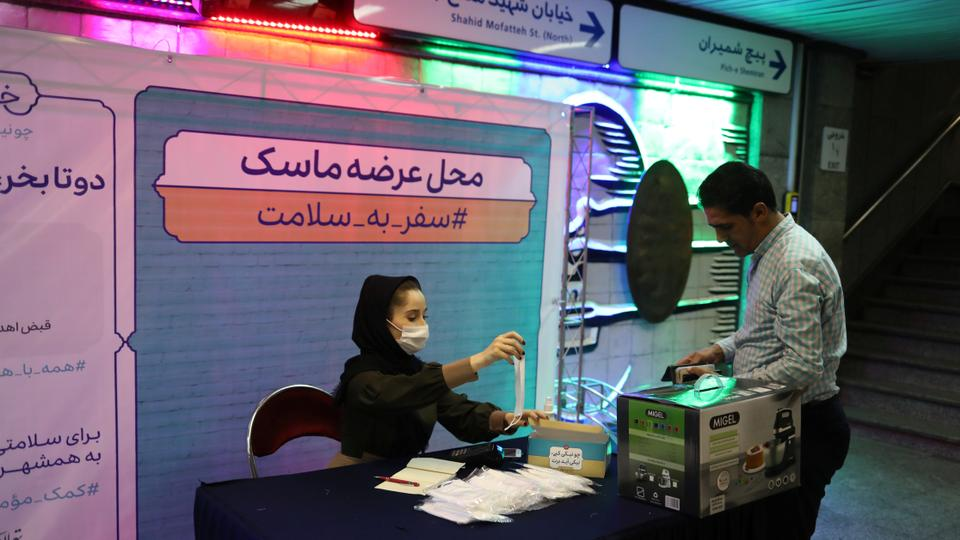 An Iranian woman sells protective face masks to a passenger in Tehran.