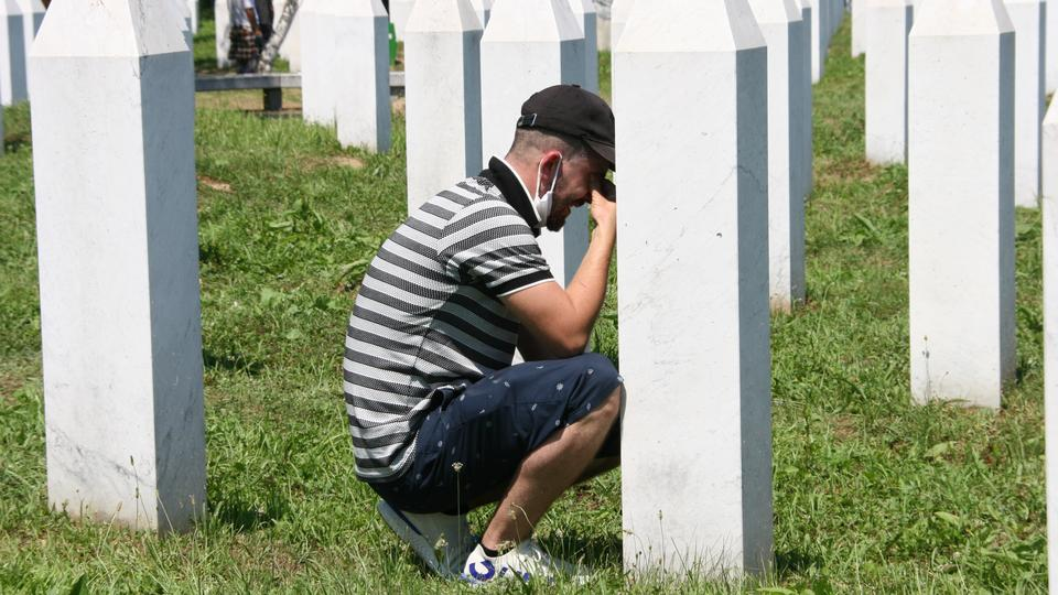 Bir adam, 11 Temmuz 2020'de Potocari'deki Srebrenica Soykırım Anıt Mezarlığı'ndaki bir mezar taşında başını ağlarken ağlıyor.