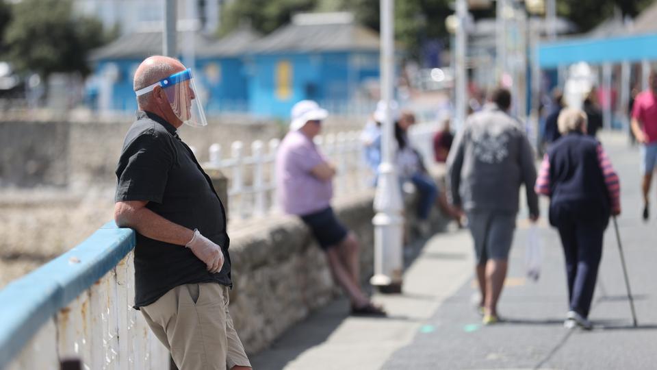 Yüz kalkanı ve eldiven takan bir adam, 11 Temmuz 2020'de İngiltere'nin Llandudno kentinde Llandudno İskelesi'nde tekrar açıldığı ilk hafta sonu resmedilmiştir.