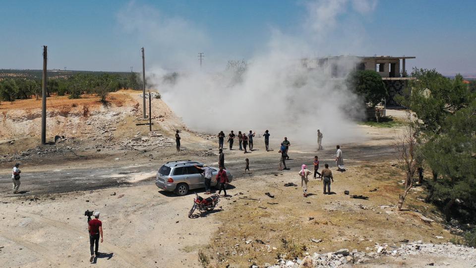 Havadan bir resim, Suriyelilerin 14 Temmuz 2020'de İdlib'in kuzeybatı muhalefetindeki Suriye'nin Ariha kasabası yakınlarında ortak bir Türk-Rus devriyesine vuran doğaçlama bir patlayıcı aygıtta toplandığını gösteriyor.