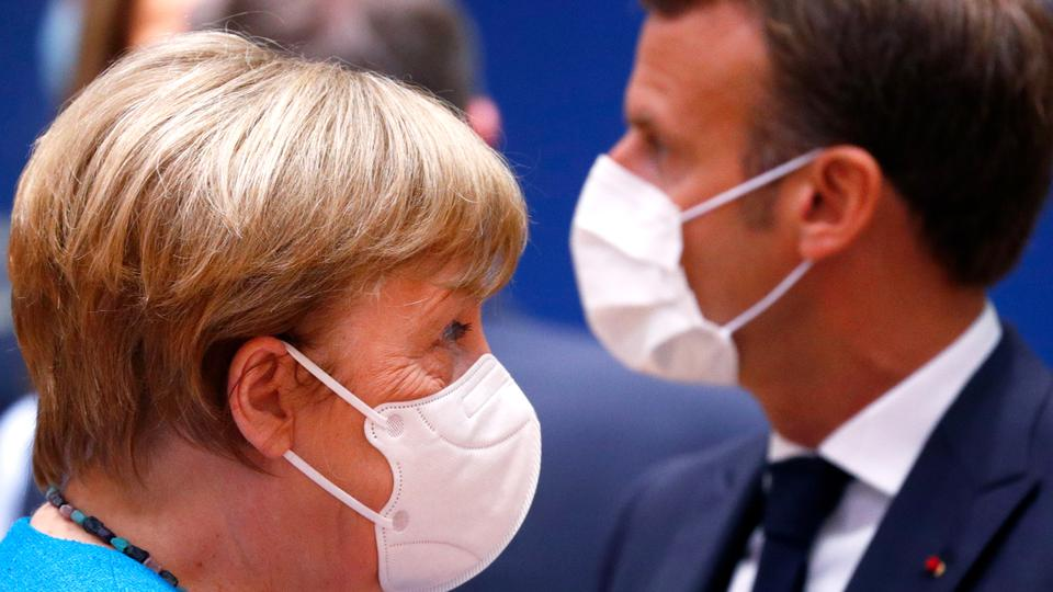 Germany's Chancellor Angela Merkel (L) and France's President Emmanuel Macron attends an EU summit at the European Council building in Brussels, on July 18, 2020