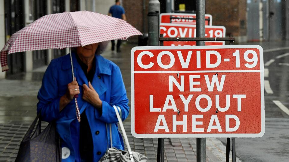 A shopper is seen walking past social distancing signs following the outbreak of the coronavirus (COVID-19) disease, in London, Britain July 1, 2020