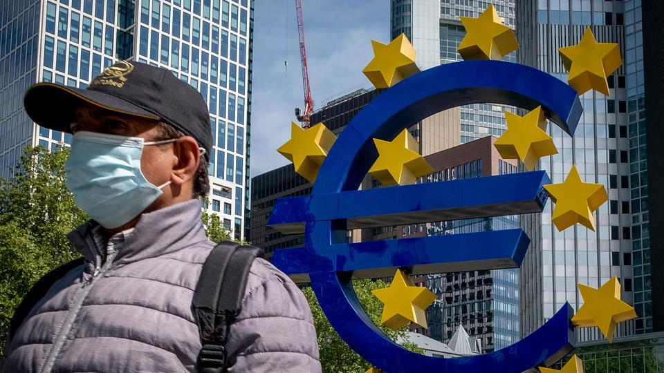 Bir adam 5 Mayıs 2020, Frankfurt, Almanya'da eski Avrupa Merkez Bankası önünde Euro heykel yürüyor.