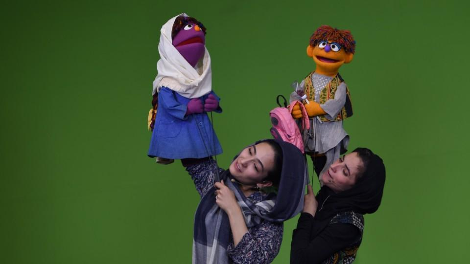 Afghan puppeteers hold new Sesame Street muppet Zeerak and muppet Zari during a recording at a television studio in Kabul on July 2, 2017