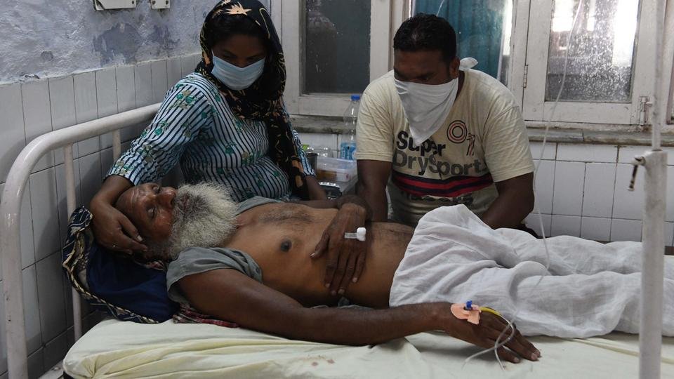 Relatives sit near the patient Sawinder Singh, who is treat at a civil hospital after allegedly drinking spurious alcohol, at Tarn Taran, August 1, 2020.
