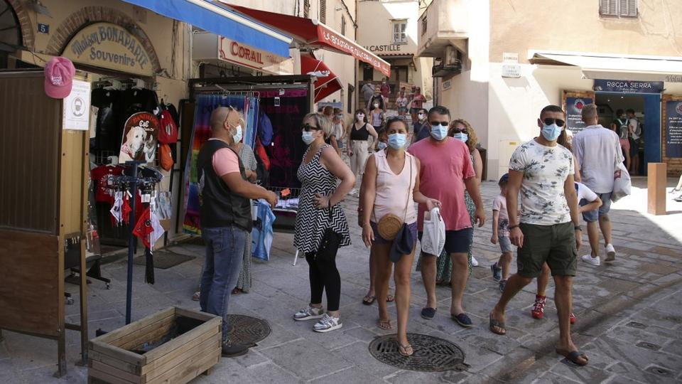 Koruyucu maskeli turistler, 5 Ağustos 2020'de eski Bonifacio şehrinin sokaklarında yürüyor.