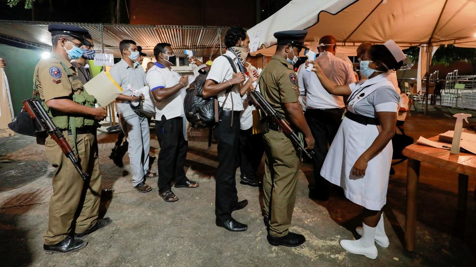 A health official takes the temperature of election officials who arrive with ballot boxes from polling station to a counting center, after the voting ended during the country's parliamentary election in Colombo, Sri Lanka, August 5, 2020.