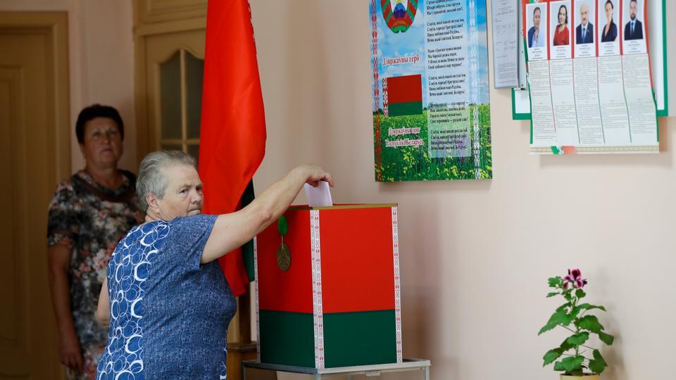 Bir kadın, 7 Ağustos 2020'de Belarus'un batı kenti Lida'da Pazar günü yapılacak seçimler öncesinde sandık başında oy pusulasını atıyor.