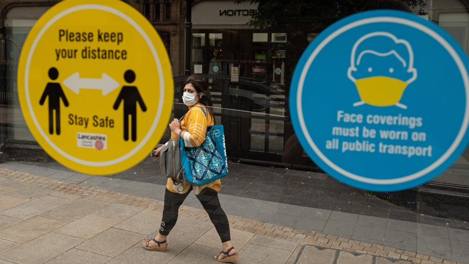 A woman walks past notices on a bus shelter advising people to maintain a social distance and wear face coverings, in the city centre of Preston, north west England on August 8, 2020.
