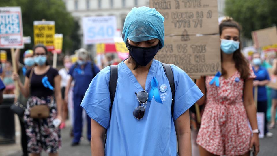 NHS (Ulusal Sağlık Servisi) çalışanları, 8 Ağustos 2020'de Londra sokaklarında bir yürüyüş sırasında koronavirüs nedeniyle hayatını kaybeden NHS personeline ücret artışı talep etmek için bir dakikalık saygı duruşunda bulundu.