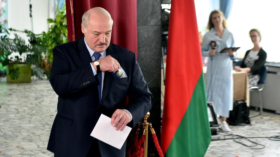 Belarus Cumhurbaşkanı Alexander Lukashenko, 9 Ağustos 2020 Minsk, Beyaz Rusya cumhurbaşkanlığı seçimleri sırasında sandık merkezinde oy kullanmadan önce bir oy pusulası ve pasaport tutuyor.
