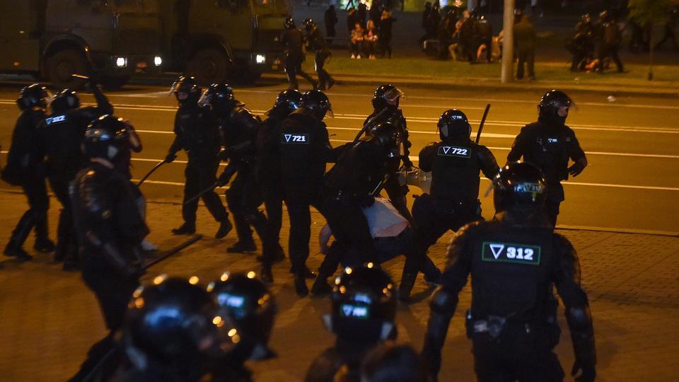 Çevik kuvvet polisi, 10 Ağustos 2020'de Minsk'te muhalefet destekçilerinin bir mitingi sırasında protestocuları gözaltına aldı.