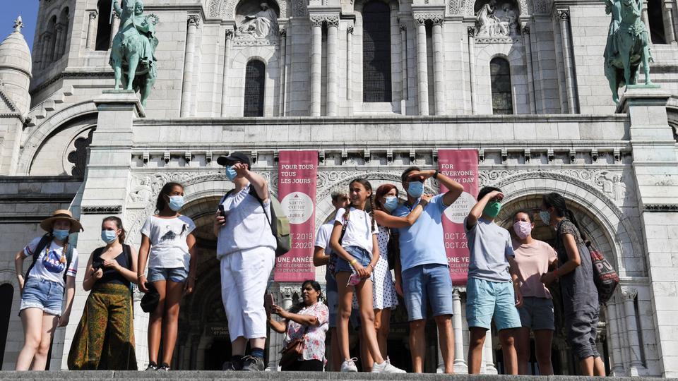Koruyucu yüz maskeleri takan insanlar, 11 Ağustos 2020'de Paris'in Montmartre semtindeki Sacre Coeur bazilikasının önünde duruyor.