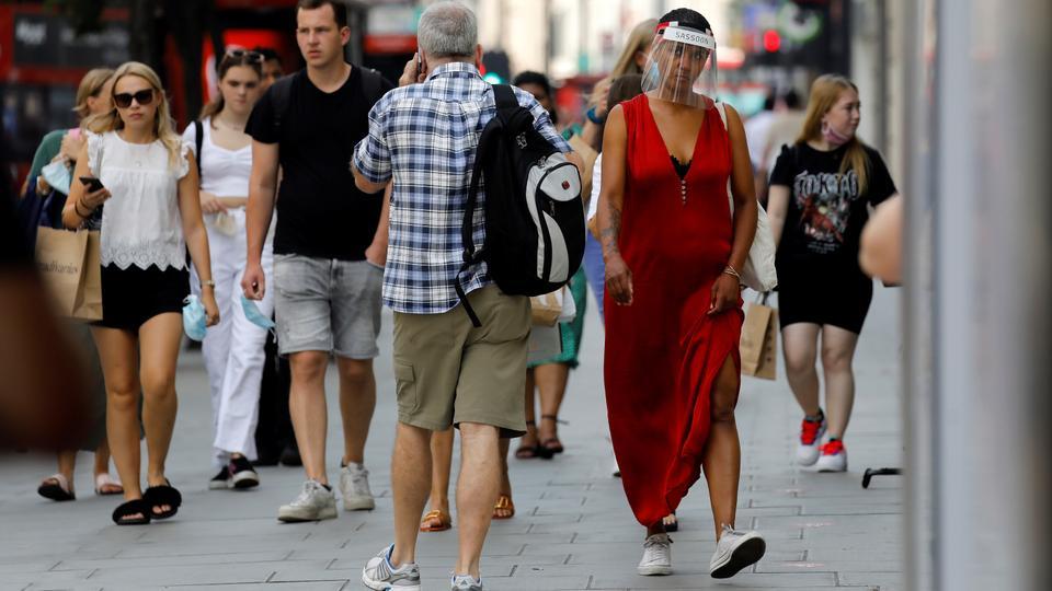 Covid-19 salgını nedeniyle yüz siperliği giyen bir kadın, alışveriş yapanlarla birlikte Londra'daki bir mağazanın önünden geçiyor. 12 Ağustos 2020.