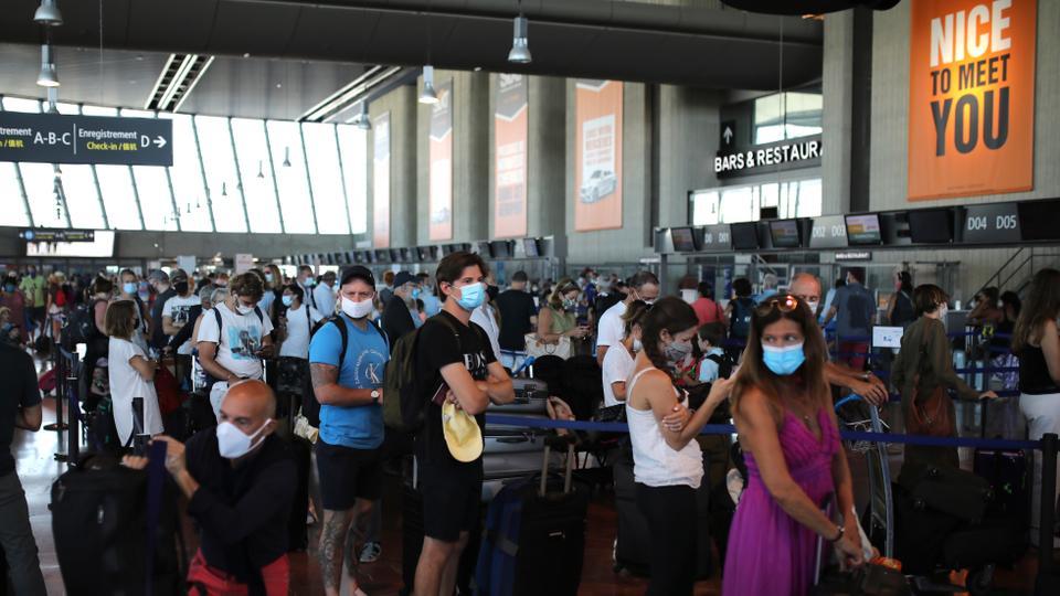 İnsanlar, British Airways'in Heathrow havaalanına, 14 Ağustos 2020, Güney Fransa'daki Nice havaalanına yapılacak bir uçuş için check-in yapmak için sırada bekliyor.