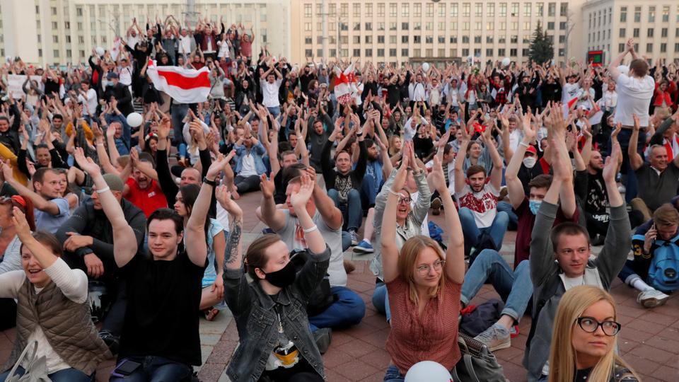 Göstericiler, polis şiddetini protesto etmek ve 14 Ağustos 2020'de Minsk, Beyaz Rusya'daki Bağımsızlık Meydanı'ndaki Hükümet Konağı yakınlarındaki cumhurbaşkanlığı seçim sonuçlarını reddetmek için bir muhalefet gösterisinde ellerini kaldırıyor.