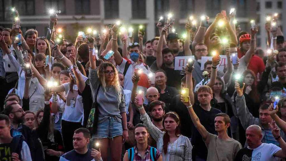 15 Ağustos 2020'de Belarus'un Minsk kentindeki Devlet TV ve radyo şirketinin yakınında sembolik bir saygı duruşu sırasında protestocular cep telefonlarını el feneriyle kaldırıyor.
