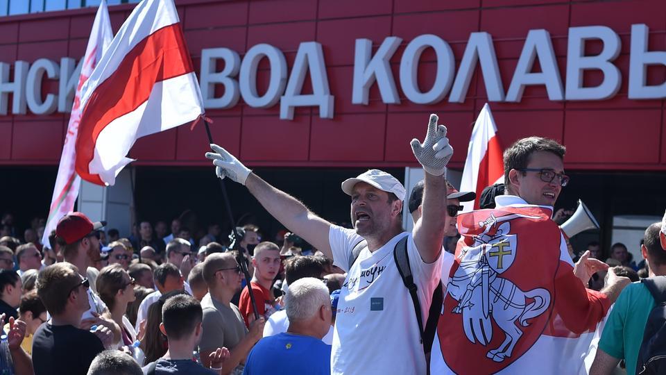 Belarus muhalefet destekçileri, 17 Ağustos 2020'de Minsk'te düzenlenen miting sırasında ağır arazi araçlarının bulunduğu MZKT fabrikası önünde toplandı.