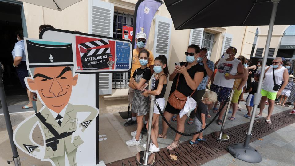 Koruyucu yüz maskesi takan turistler Fransa'nın Saint Tropez kentindeki Jandarma ve Sinema Müzesi'ni ziyaret etmek için sıraya girdi, 17 Ağustos 2020.