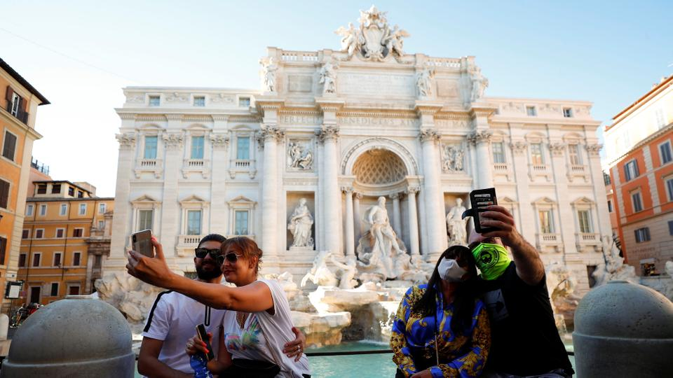 A couple wears face masks while other couple does not as they both take selfies in front of the Trevi Fountain, Italy on August 19, 2020.