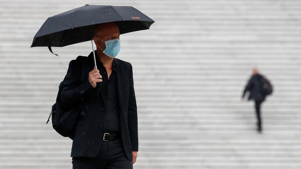 Koruyucu maske takan bir adam 17 Ağustos 2020'de Fransa'nın Paris kenti yakınlarındaki La Defense'nin finans ve ticaret bölgesinde yürüyor