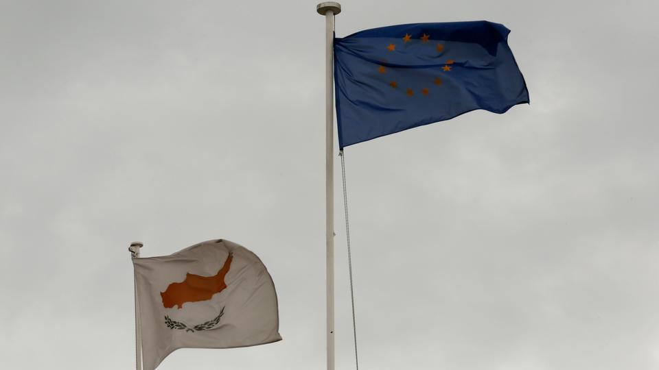 Avrupa Birliği ve Kıbrıs Rumlarının yönettiği Kıbrıs bayrakları, 22 Şubat 2013'te Lefkoşa'daki cumhurbaşkanlığı sarayının tepesinde dalgalanıyor.