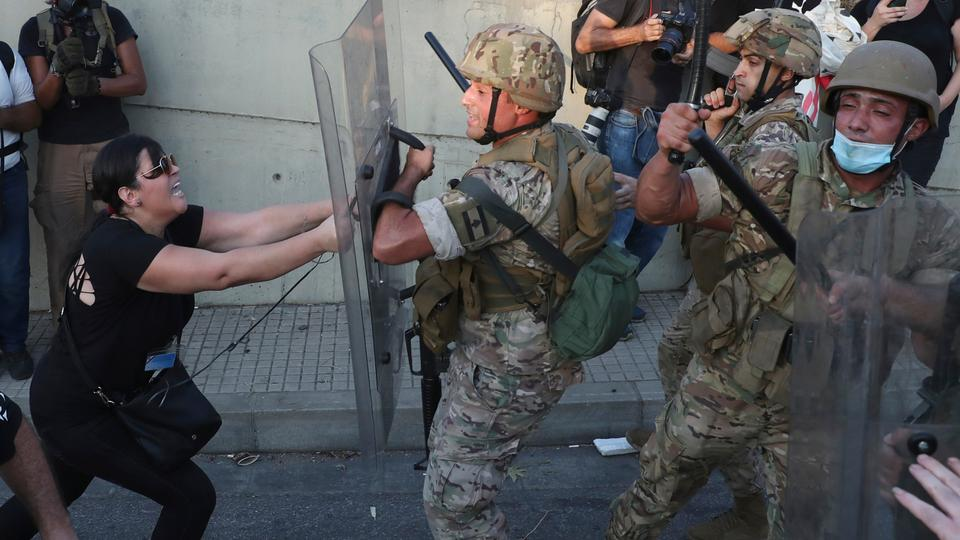 An anti-government protester clashes with Lebanese soldiers in Baabda east of Beirut, Lebanon, Saturday, Sept. 12, 2020.