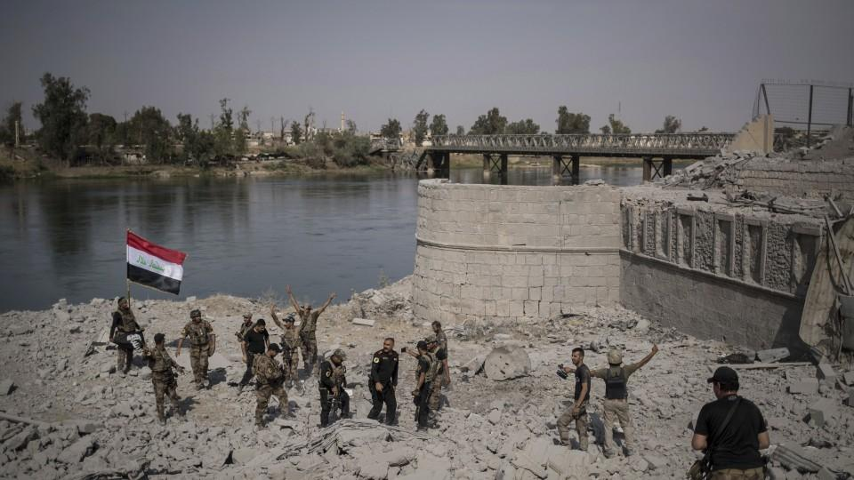 Iraqi Special Forces soldiers celebrate after reaching the bank of the Tigris river during their fight against Daesh in Mosul, 2017.