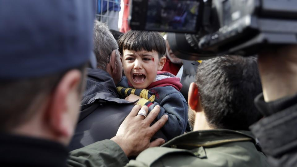 Greek Migration Minister Yannis Mouzalas holds a slightly injured boy as Afghan migrants block the entrance at the Hellenikon migrant camp, in southern Athens, Monday, Feb. 6, 2017.