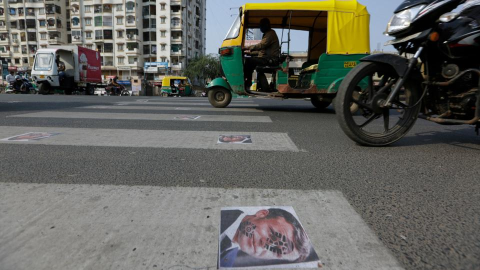 Indian commuters move on defaced images of French President Emmanuel Macron pasted by protestors on a road in Ahmedabad, India. November 1, 2020.