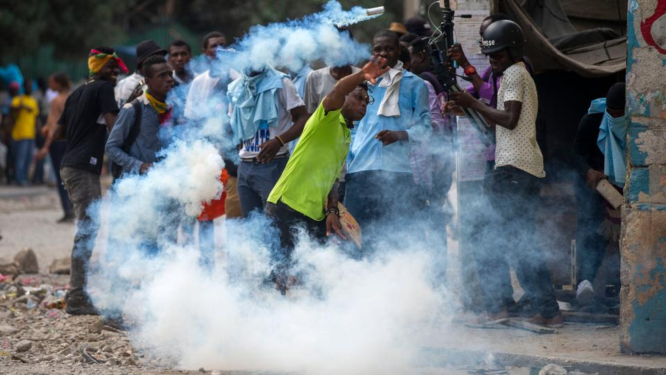 A protester throws back a tear gas canister launched by police attempting to disperse protesters demanding answers, in Port-au-Prince, Haiti, November 5, 2020.