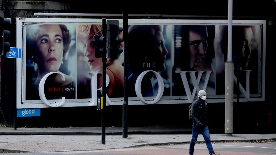 A man wearing a face mask walks past a billboard advertising 'The Crown' television series in London, Friday, Nov. 20, 2020.