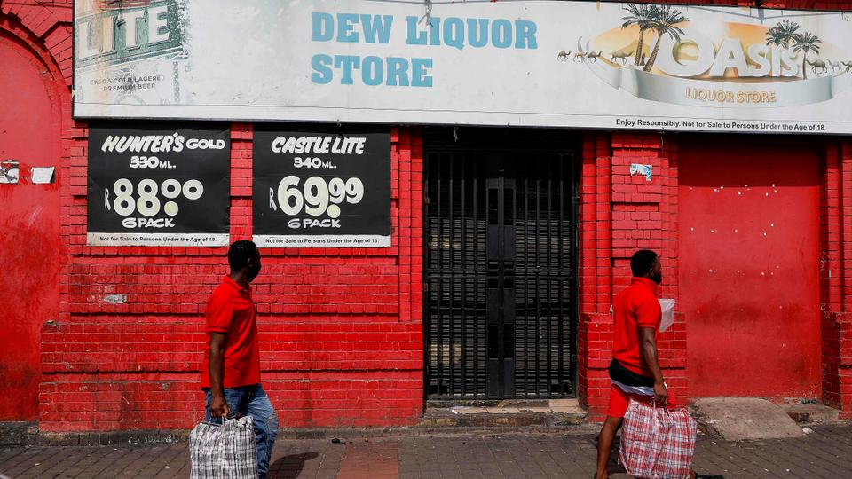 People walk past a closed liquor store in Johannesburg CBD on December 29, 2020.